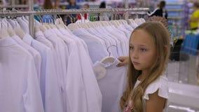 Muchacha del adolescente que elige la blusa blanca en tienda de ropa Moda y compras almacen de metraje de vídeo
