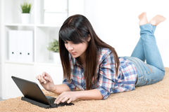 Muchacha del adolescente que estudia en casa la mentira en el sofá Fotografía de archivo libre de regalías