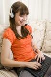 Muchacha del adolescente que habla con el receptor de cabeza y la computadora portátil Imagen de archivo libre de regalías
