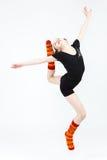 Muchacha del adolescente que hace danza de la gimnasia en el salto en un blanco Fotos de archivo