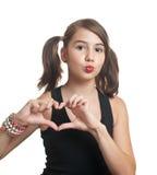 Muchacha del adolescente que hace dimensión de una variable del corazón con sus manos Foto de archivo libre de regalías