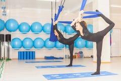 Muchacha del adolescente que hace estirar y la guita, yoga aérea Imagenes de archivo