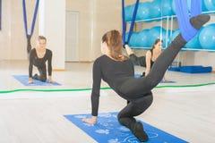 Muchacha del adolescente que hace estirar y la guita, yoga aérea Imagen de archivo libre de regalías