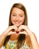 Muchacha del adolescente que hace la cereza de la explotación agrícola de la dimensión de una variable del corazón Fotos de archivo libres de regalías