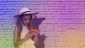 Muchacha del adolescente que hojea el teléfono móvil en fondo de la pared de ladrillo en luz colorida Chica joven que usa el smar almacen de metraje de vídeo