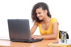 Muchacha del adolescente que hojea en un ordenador portátil en el escritorio Imagen de archivo libre de regalías