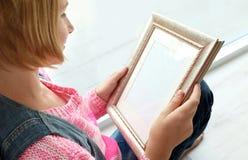 Muchacha del adolescente que lleva a cabo el marco de la foto y que se sienta cerca de ventana Fotografía de archivo