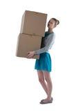 Muchacha del adolescente que lleva las cajas pesadas Foto de archivo libre de regalías