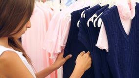 Muchacha del adolescente que mira la ropa en tienda de moda cámara lenta 4k almacen de metraje de vídeo