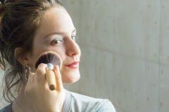 Muchacha del adolescente que mira a su uno mismo en un espejo que aplica el polvo a él Imágenes de archivo libres de regalías