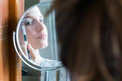 Muchacha del adolescente que mira a su uno mismo en un espejo redondo que aplica eyesha Fotografía de archivo libre de regalías