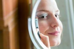 Muchacha del adolescente que mira a su uno mismo en un espejo redondo que aplica eyesha Foto de archivo libre de regalías