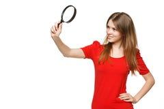 Muchacha del adolescente que mira a través de la lupa Imagen de archivo
