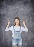 Muchacha del adolescente que muestra la muestra de la victoria en el fondo de la pizarra Imagenes de archivo