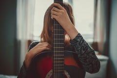 Muchacha del adolescente que oculta detrás de la guitarra Foto de archivo