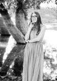 Muchacha del adolescente que presenta en bosque natural en negro del vestido y w largos Imagen de archivo libre de regalías