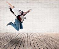 Muchacha del adolescente que salta con la guitarra eléctrica Imagenes de archivo