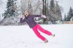 Muchacha del adolescente que salta y que lanza una bola de nieve Foto de archivo