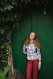 Muchacha del adolescente que se coloca cerca de puerta verde vieja Imagen de archivo