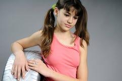 Muchacha del adolescente que se coloca en los neumáticos de plata Foto de archivo