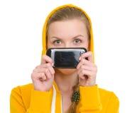 Muchacha del adolescente que se considera móvil delante de cara Fotografía de archivo libre de regalías