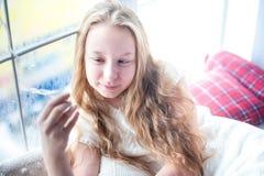 Muchacha del adolescente que se sienta cerca de la ventana y que sostiene una guirnalda Imágenes de archivo libres de regalías
