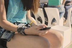 Muchacha del adolescente que se sienta con el teléfono móvil a disposición Foto de archivo
