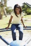 Muchacha del adolescente que se sienta en cruce giratorio del patio Fotografía de archivo