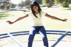 Muchacha del adolescente que se sienta en cruce giratorio del patio Imágenes de archivo libres de regalías