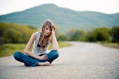 Muchacha del adolescente que se sienta en el camino Imagenes de archivo