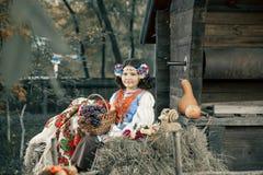 Muchacha del adolescente que se sienta en el heno que lleva una guirnalda y un traje ucraniano nacional al lado de la cesta de fr Fotos de archivo
