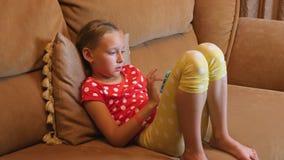 Muchacha del adolescente que se sienta en el sofá usando el teléfono móvil en interior acogedor del sitio metrajes