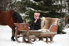 Muchacha del adolescente que se sienta en el trineo con las pieles y el caballo marrón Imágenes de archivo libres de regalías