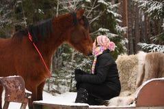 Muchacha del adolescente que se sienta en el trineo con las pieles y el caballo marrón Foto de archivo libre de regalías