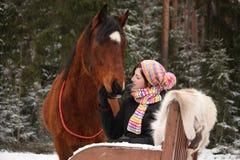Muchacha del adolescente que se sienta en el trineo con las pieles y el caballo marrón Imagen de archivo