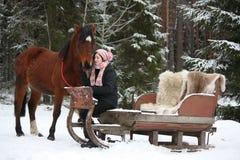 Muchacha del adolescente que se sienta en el trineo con las pieles y el caballo marrón Fotos de archivo libres de regalías