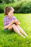 Muchacha del adolescente que se sienta en hierba con la tableta digital Fotografía de archivo