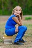 Muchacha del adolescente que se sienta en pila Fotos de archivo
