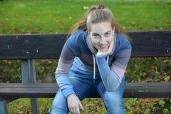 Muchacha del adolescente que se sienta en un banco Imagenes de archivo