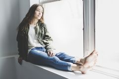 Muchacha del adolescente que se sienta en ventana Fotografía de archivo libre de regalías