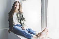 Muchacha del adolescente que se sienta en ventana Fotografía de archivo