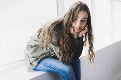 Muchacha del adolescente que se sienta en ventana Imagenes de archivo