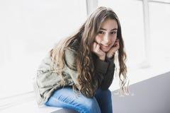 Muchacha del adolescente que se sienta en ventana Imágenes de archivo libres de regalías