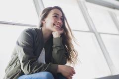 Muchacha del adolescente que se sienta en ventana Imagen de archivo libre de regalías