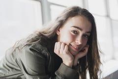 Muchacha del adolescente que se sienta en ventana Foto de archivo