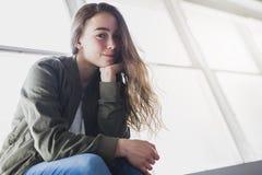 Muchacha del adolescente que se sienta en ventana Fotos de archivo