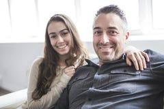 Muchacha del adolescente que se sienta en ventana con el padre Fotografía de archivo