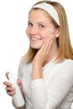 Muchacha del adolescente que sonríe aplicando la loción de la crema hidratante  Fotos de archivo