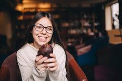 Muchacha del adolescente que sonríe y que sostiene una magdalena Foto de archivo libre de regalías