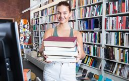 Muchacha del adolescente que sostiene una pila de libros en una librería Imagen de archivo